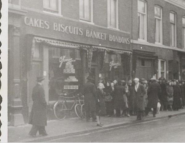 1942 Lange rij wachtenden voor banketbakkerswinkel Jamin op de Ho