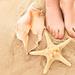 zomer-achtergrond-met-blote-voeten-in-het-zand-op-het-strand-met-