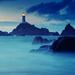 foto-van-een-vuurtoren-op-een-eiland-en-met-zee-en-rotsen-er-omhe
