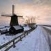 mooi-hollands-winterlandschap-met-een-molen-langs-een-weg-en-over